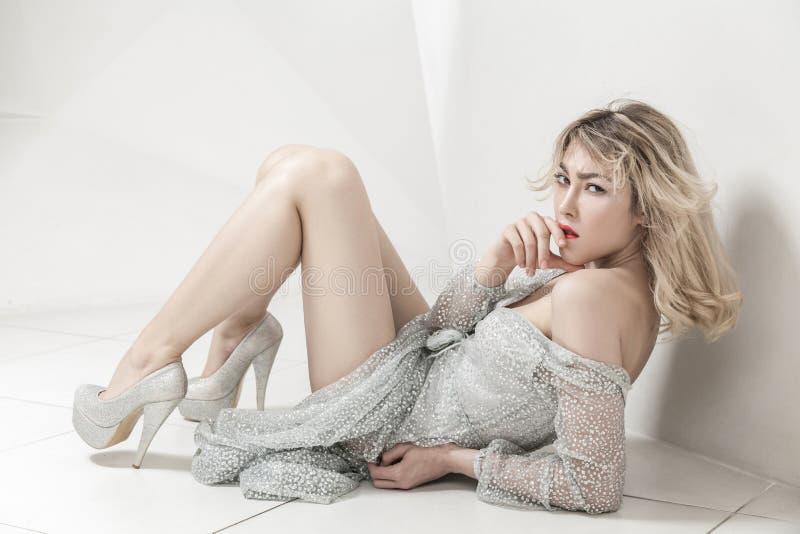 坐砖地和诱人的看的照相机和bitting她的嘴唇的灰色银色透明礼服的白肤金发的妇女 免版税库存照片