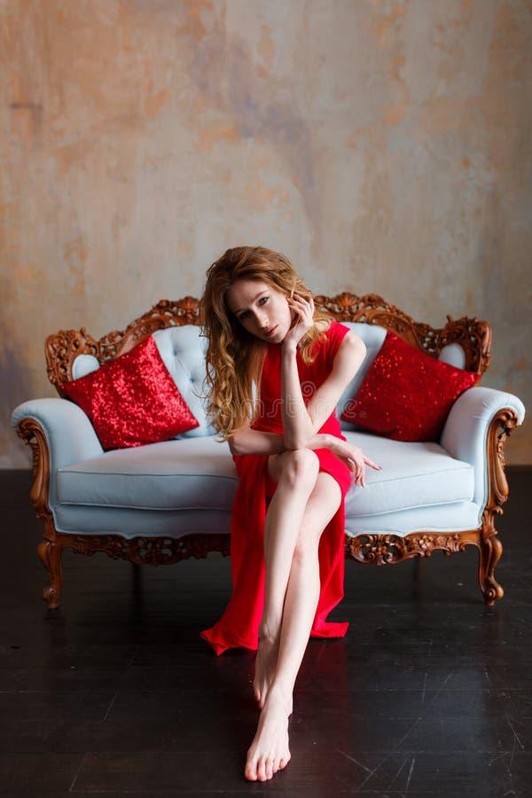 坐经典沙发和看照相机的红色礼服的典雅的肉欲的年轻redhair妇女 与电灯泡的顶楼内部 图库摄影