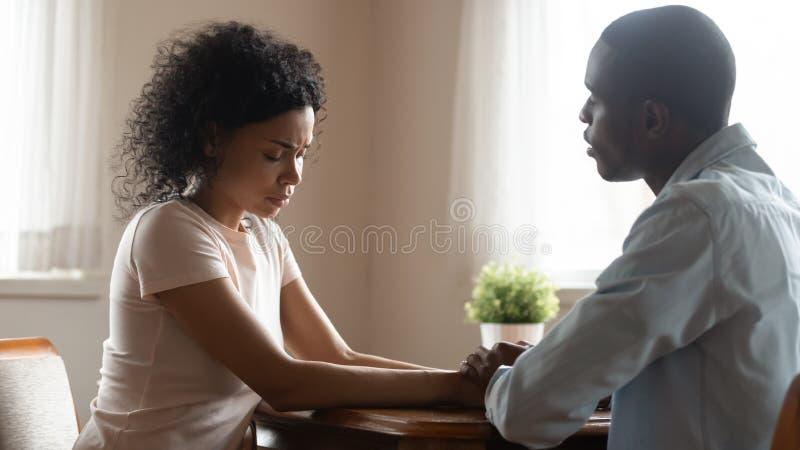 坐结合在一起使手爱丈夫的配偶安慰哀伤的妻子 免版税库存图片
