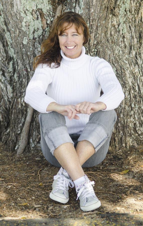 坐结构树的愉快的妇女。 免版税库存照片