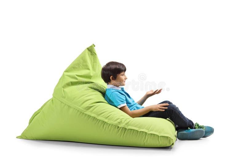坐绿豆袋子和打手势用手的男孩 免版税图库摄影