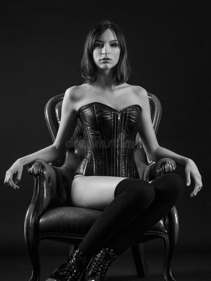 坐美丽的妇女穿束腰 免版税库存照片