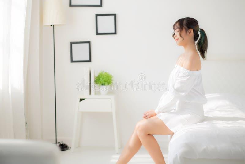 坐美丽的年轻亚裔的妇女画象看窗口和微笑一会儿醒与日出在早晨 库存图片