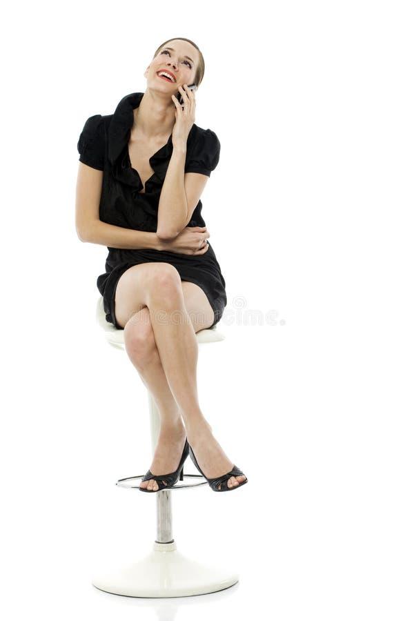 坐聪明的凳子妇女的移动电话藏品 图库摄影