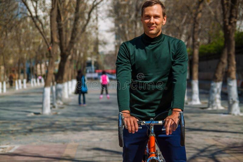坐自行车和smilling在城市的英俊的年轻人 库存照片