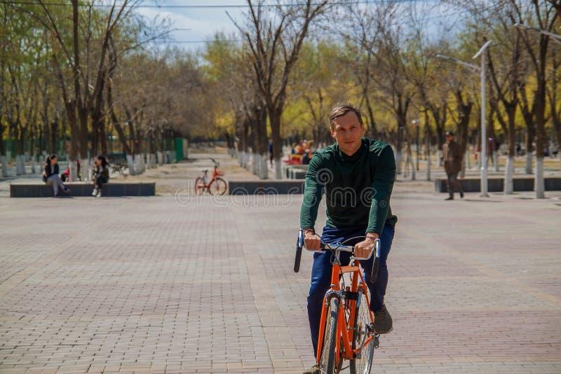 坐自行车和smilling在城市的英俊的年轻人 图库摄影