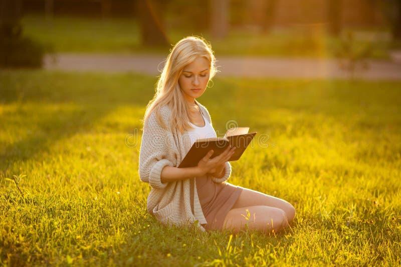坐草和读书的女孩 免版税库存图片