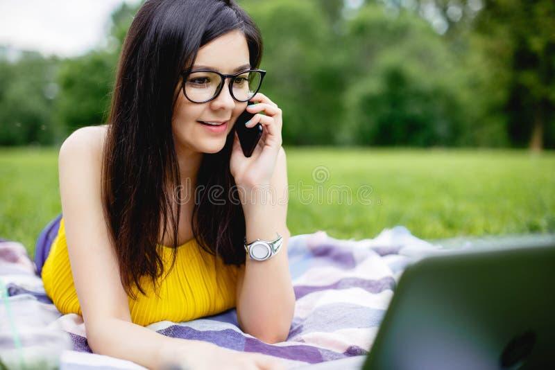 坐草在明亮的夏日和研究计算机的微笑的女孩 使用膝上型计算机户外,聊天与朋友, 库存图片