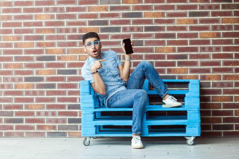 坐蓝色木板台和指向在的震惊年轻有胡子的人和镜片全长画象便装样式的 库存照片