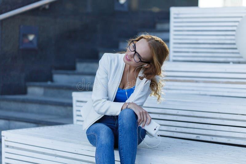 坐街道台阶和听到音乐的女孩在电话 库存照片