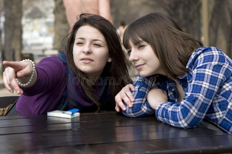 坐街道青少年二的咖啡馆女孩 免版税库存照片