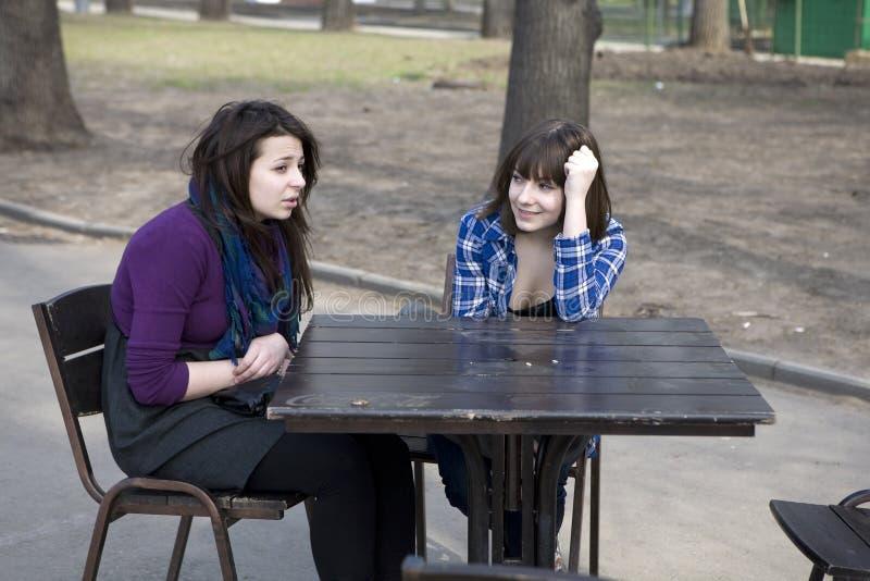 坐街道青少年二的咖啡馆女孩 免版税图库摄影