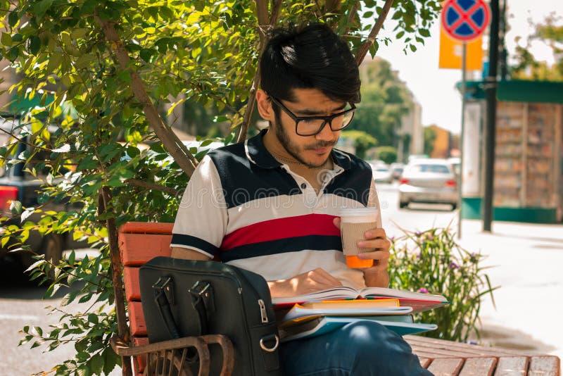 坐街道饮用的咖啡和读书玻璃的英俊的人 免版税库存照片
