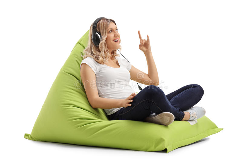 坐装豆子小布袋和听到音乐的少妇 免版税图库摄影