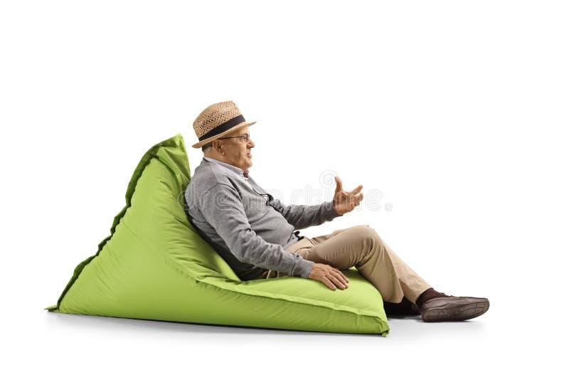 坐装豆子小布袋和打手势用手的老人 库存照片