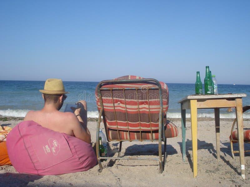 坐装豆子小布袋和读书的海滨的人 库存照片