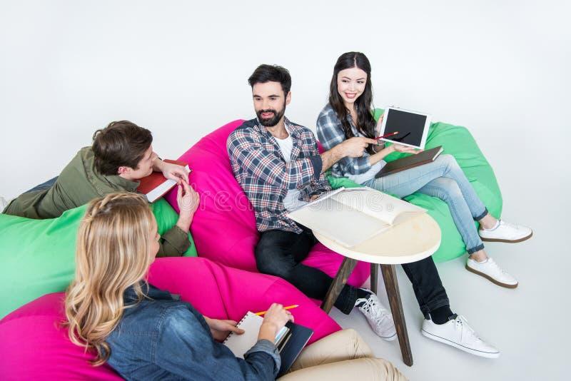 坐装豆子小布袋椅子和学习与数字式片剂的学生在演播室 免版税库存照片