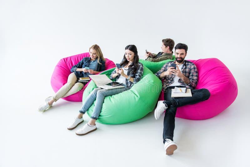 坐装豆子小布袋椅子和学习和使用智能手机的学生在演播室 库存照片