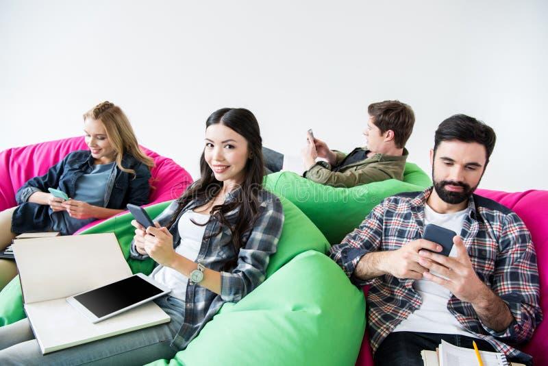 坐装豆子小布袋椅子和学习和使用智能手机的学生在演播室 库存图片