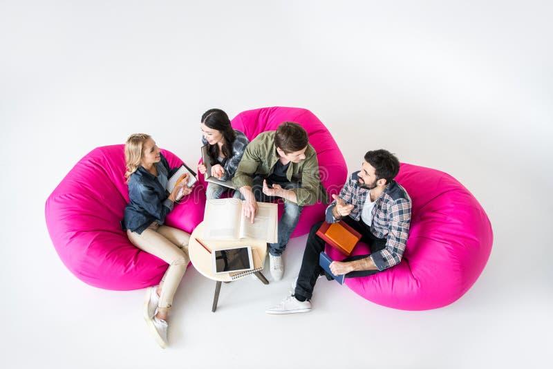 坐装豆子小布袋椅子和学习在演播室的学生 库存图片