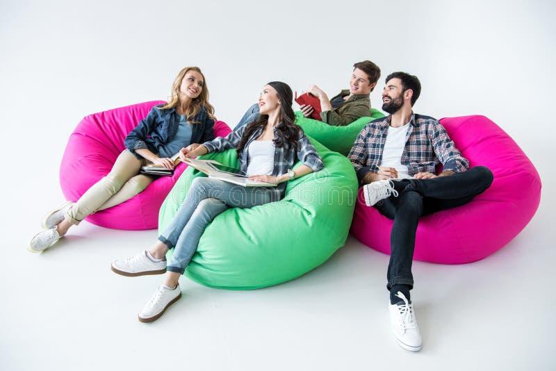 坐装豆子小布袋椅子和学习在演播室的学生 免版税图库摄影