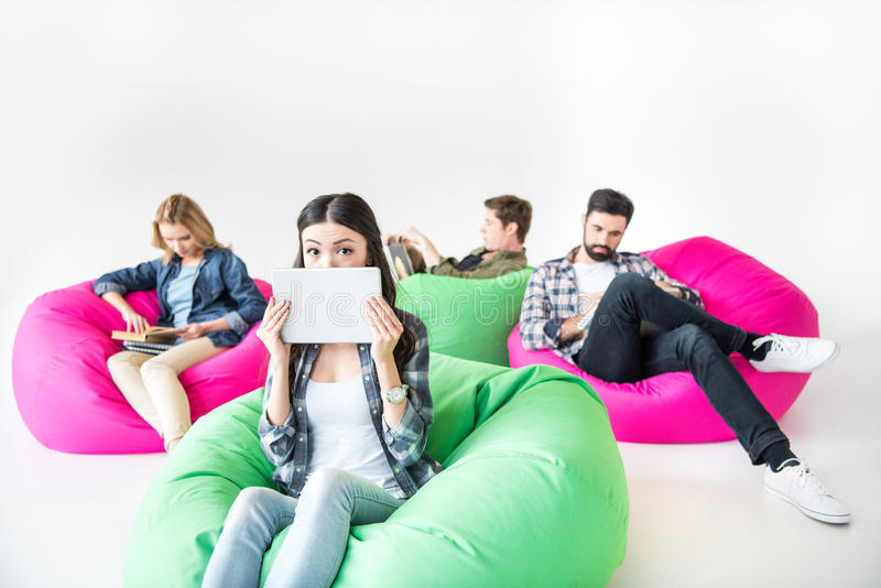 坐装豆子小布袋椅子和学习在演播室的学生 图库摄影
