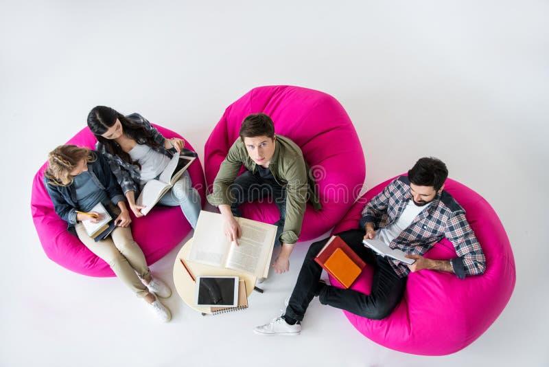 坐装豆子小布袋椅子和学习在演播室的顶上的观点的学生 库存照片