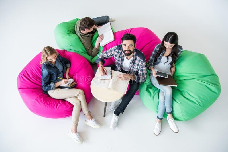 坐装豆子小布袋椅子和学习在演播室的顶上的观点的学生 免版税库存图片