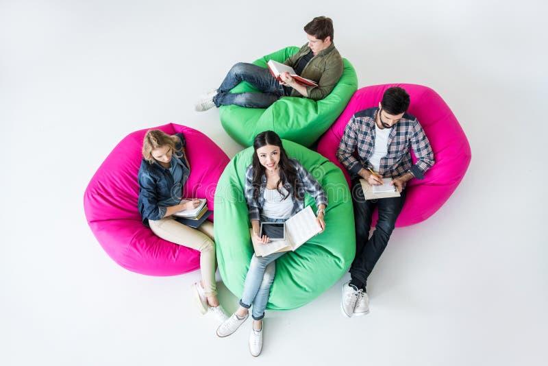 坐装豆子小布袋椅子和学习在演播室的顶上的观点的学生 免版税库存照片