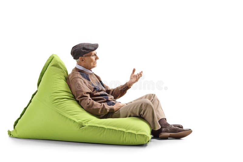坐辎重袋和打手势用手的老人 图库摄影