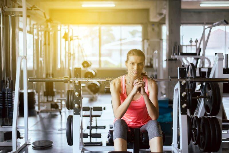 坐适合的妇女和在健身房的健康训练的概念和生活方式以后放松,女性休假在锻炼a以后 免版税库存照片