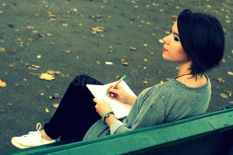 坐长凳和写入日志的美丽的深色的女孩 免版税库存图片