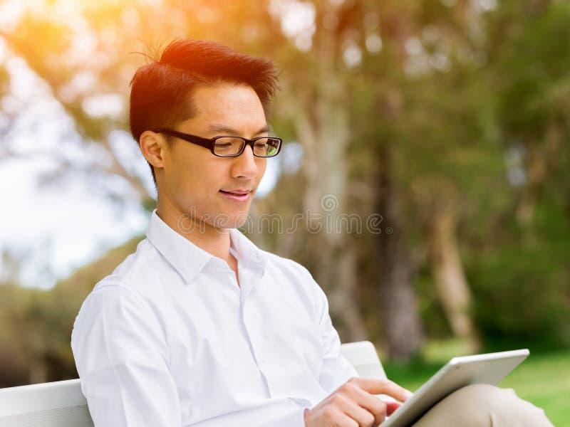 坐长凳和写在笔记薄的可爱的周道的商人 图库摄影