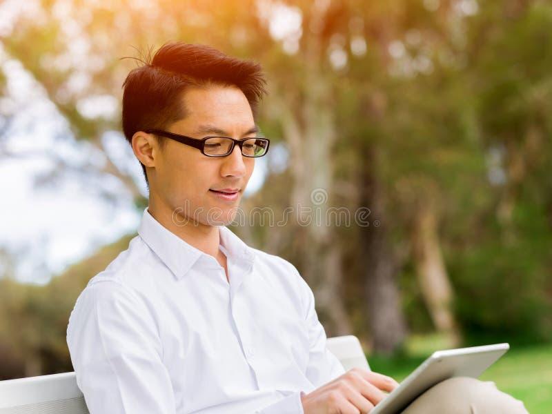 坐长凳和写在笔记薄的可爱的周道的商人 免版税图库摄影