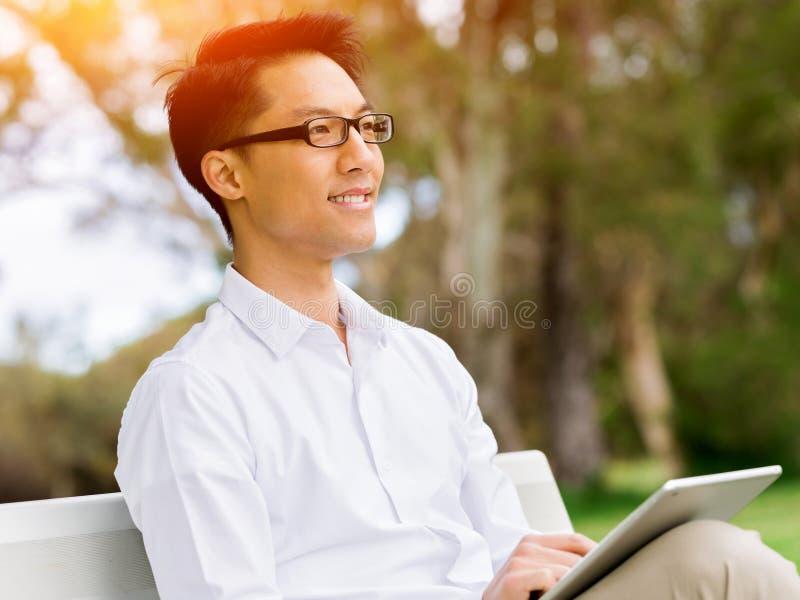 坐长凳和写在笔记薄的可爱的周道的商人 免版税库存照片