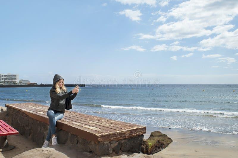 坐长凳和拍摄与后边她的海岸的电话的可爱的白种人妇女照片 库存照片
