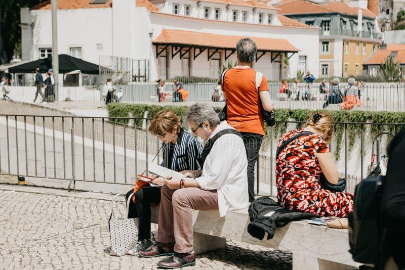 坐长凳和看一张地图的成熟夫妇在里斯本在葡萄牙 免版税库存图片