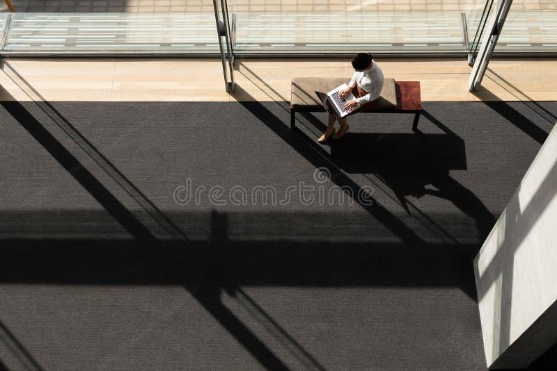 坐长凳和研究膝上型计算机的白种人女实业家在办公室 免版税库存图片
