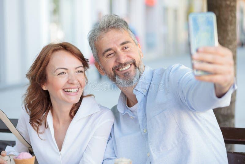 坐长凳和采取selfie的愉快的成熟游人夫妇 免版税库存图片