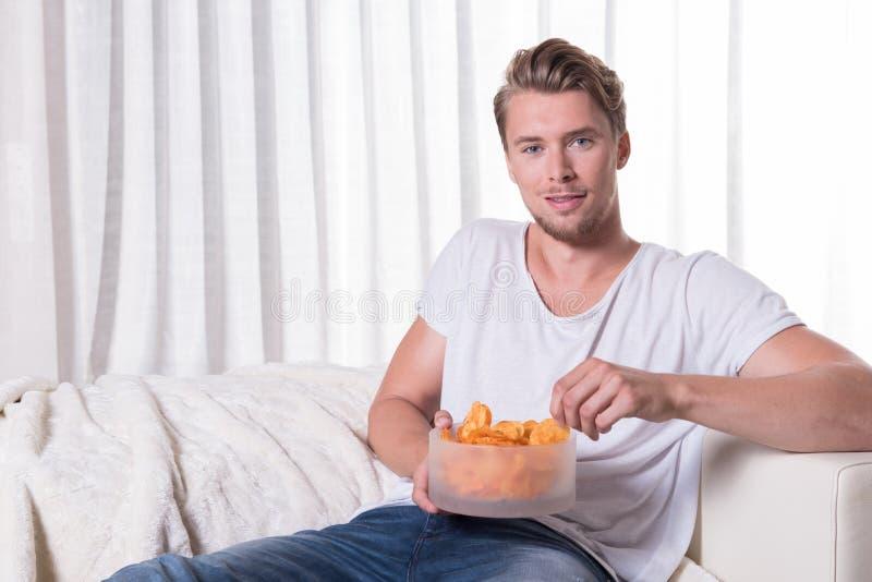 坐长沙发和吃芯片的画象年轻人 库存图片