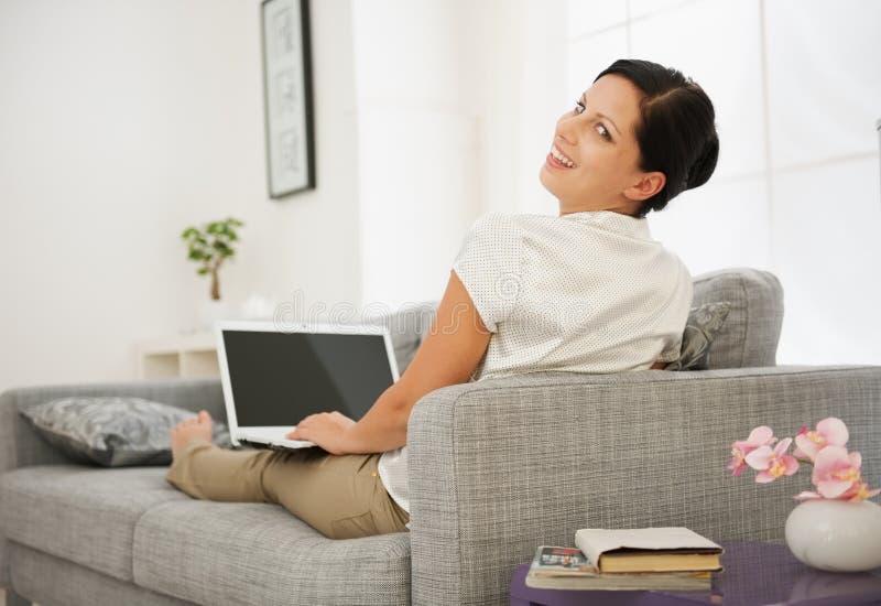 坐长沙发和研究膝上型计算机的妇女 库存图片