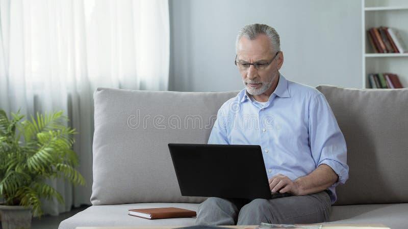 坐长沙发和研究膝上型计算机的男性新闻工作者,做自由职业者和行业 库存照片