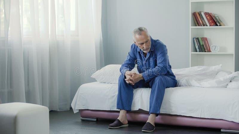 坐长沙发和考虑他的健康,早晨的资深孤独的人 免版税图库摄影