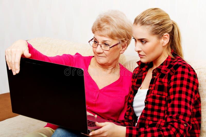 坐长沙发和观看某事的母亲和女儿在膝上型计算机 免版税库存图片