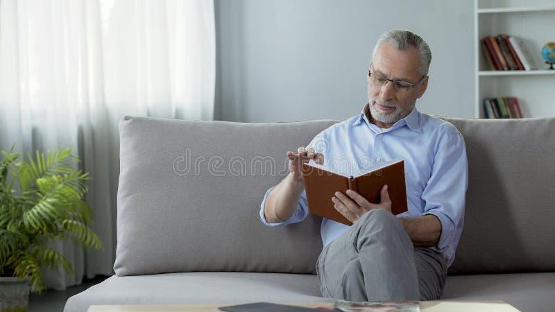 坐长沙发和读周末计划、爱好和业余时间的愉快的老人 免版税库存图片