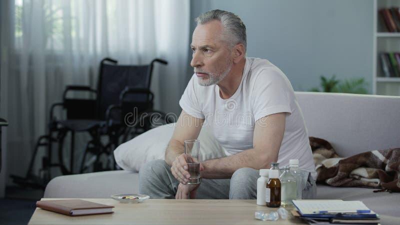 坐长沙发和采取药片、寂寞和悲伤的老有残障的男性 库存照片