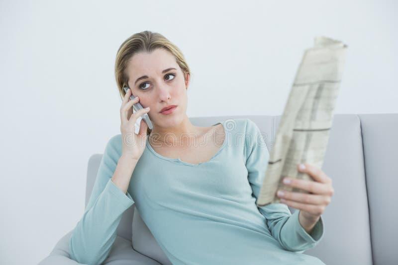 给坐长沙发打电话的偶然严肃的妇女 库存图片
