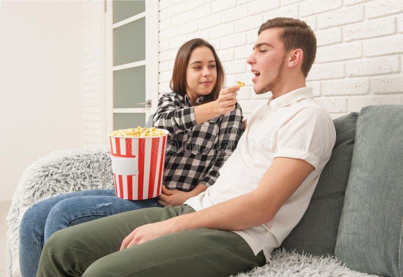 坐长沙发看电视的两个少年 免版税库存照片