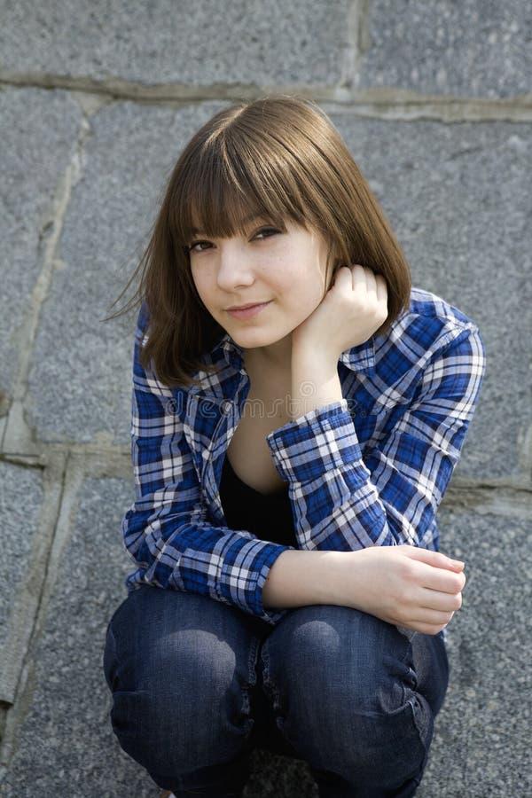 坐青少年的年轻人的女孩纵向 免版税库存照片