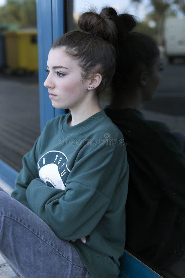 坐,不用看的青少年的女孩照相机 免版税库存照片